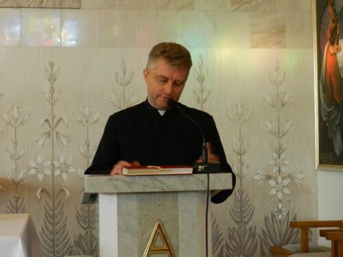Zdjęcie przedstawia księdza przemawiającego na ambonie.