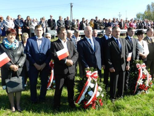 Zdjęcie przedstawia ludzi z wieńcem podczas obchodów 100 rocznicy odzyskania przez Polskę niepodległości.
