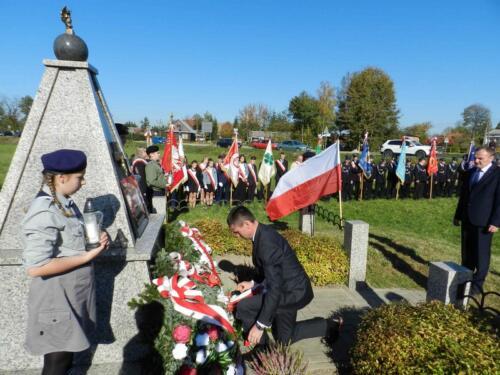 Zdjęcie przedstawia harcerzy oraz innych ludzi przy pomniku podczas obchodów 100 rocznicy odzyskania przez Polskę niepodległości.