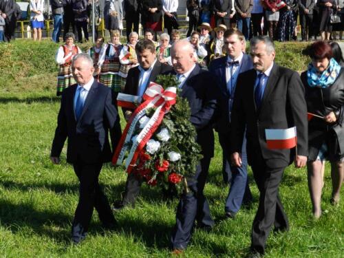 Zdjęcie przedstawia ludzi idących z wieńcem podczas obchodów 100 rocznicy odzyskania przez Polskę niepodległości.