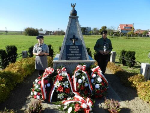 Zdjęcie przedstawia harcerzy przy pomniku podczas obchodów 100 rocznicy odzyskania przez Polskę niepodległości.