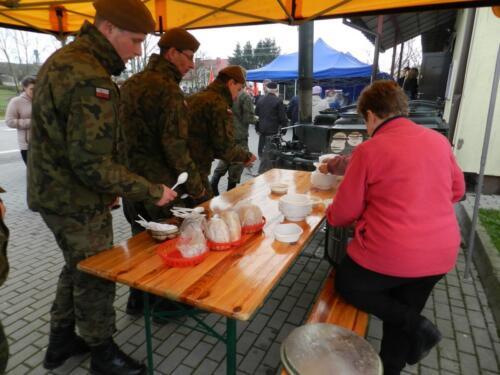 Zdjęcie przedstawia żołnierzy oraz cywila którzy konsumują jakieś danie.
