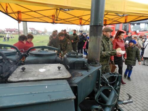 Zdjęcie przedstawia kuchnię polową oraz ludzi w tle.