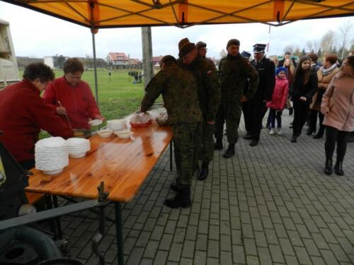 Zdjęcie przedstawia żołnierzy którzy czekają w kolejce po jedzenie.