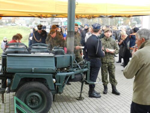 Zdjęcie przedstawia żołnierzy i innych ludzi którzy czekają w kolejce po jedzenie.