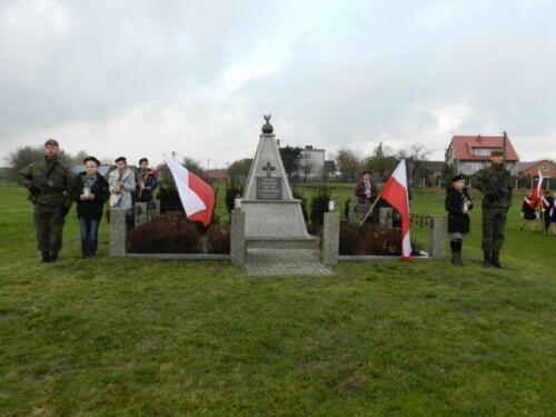 Zdjęcie przedstawia pomnik oraz ludzi przy nim stojących.