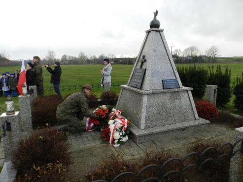 Zdjęcie przedstawia złożenie kwiatów pod pomnikiem przez żołnierza.