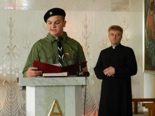 Zdjęcie przedstawia harcerza czytającego pismo podczas mszy świętej podczas obchodów 100 rocznicy odzyskania przez Polskę niepodległości.
