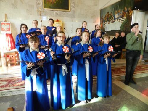 Zdjęcie przedstawia ludzi w chórze  w kościele podczas obchodów 100 rocznicy odzyskania przez Polskę niepodległości.