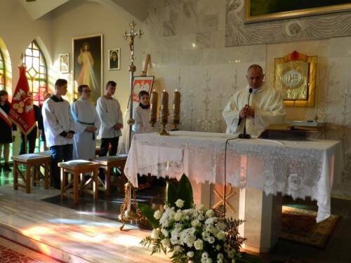 Zdjęcie przedstawia księdza który odprawia mszę świętą i ministrantów w tle.