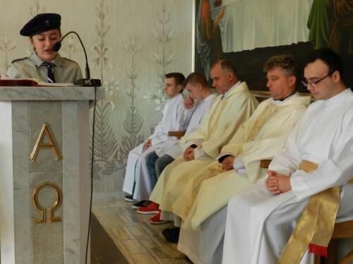 Zdjęcie przedstawia harcerkę w kościele podczas obchodów 100 rocznicy odzyskania przez Polskę niepodległości, oraz w tle widać księży którzy odprawiają tę mszę świętą.