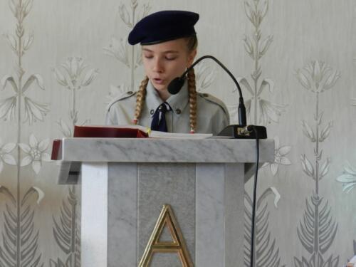 Zdjęcie przedstawia harcerkę w kościele podczas obchodów 100 rocznicy odzyskania przez Polskę niepodległości.