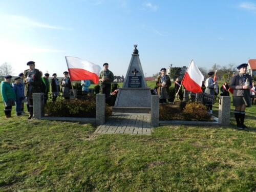 Zdjęcie przedstawia ludzi podczas obchodów 100 rocznicy odzyskania przez Polskę niepodległości przy pomniku.