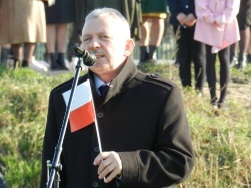 Zdjęcie przedstawia starego człowieka z flagą Polską wygłaszającego przemówienie.