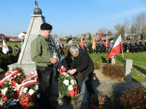 Zdjęcie przedstawia ludzi podczas obchodów 100 rocznicy odzyskania przez Polskę niepodległości idących z wieńcem przy pomniku.