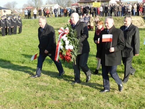 Zdjęcie przedstawia ludzi podczas obchodów 100 rocznicy odzyskania przez Polskę niepodległości idących z wieńcem.