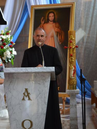 Zdjęcie przedstawia księdza mówiącego coś w kościele na ambonie.