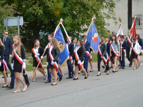 Zdjęcie przedstawia uczniów szkół idących ulicami gminy na obchodach związanych z rocznicą wybuchu II Wojny Światowej.