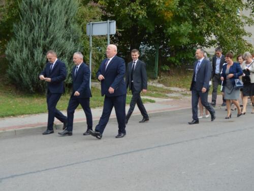 Zdjęcie przedstawia oficjeli idących ulicami gminy na obchodach związanych z rocznicą wybuchu II Wojny Światowej.