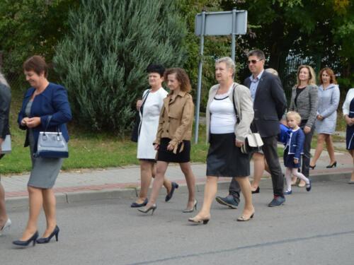 Zdjęcie przedstawia ludzi idących ulicą miasta na obchodach związanych z rocznicą wybuchu II Wojny Światowej.
