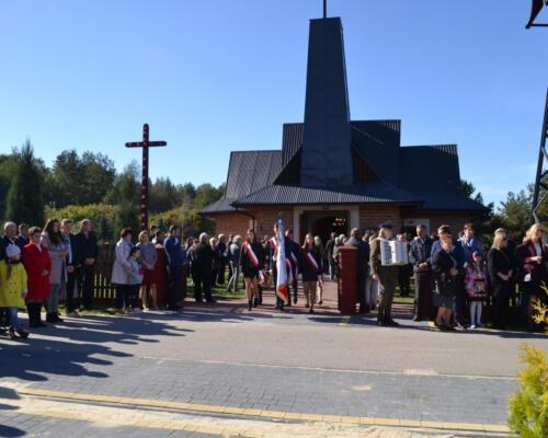 Zdjęcie przedstawia złożenie hołdu pomordowanym ludziom przez Niemców we wsi Osówek przy kościele przez współczesnych ludzi.