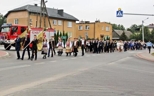 Zdjęcie prezentuje idącą grupę ludzi ubranych w stroje świąteczne i niosące z przodu flagi