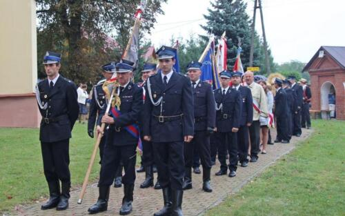 Zdjęcie przedstawia grupę ludzi ubranych w stroje i trzymających flagi