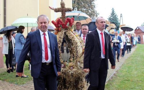 Zdjęcie przedstawia jak dwa człowieka niosą wielką figurę dożynkową