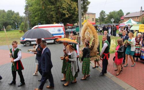 Zdjęcie przedstawia grupę ludzi ubranych w stroje świąteczne z figurą dożynkową