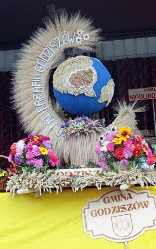 """Zdjęcie przedstawia trofeum przypominającym globus, zrobiony z materiałów naturalnych z napisem """"Gmina Godziszów"""""""