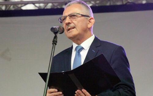 Zdjęcie przedstawia człowieka mówiącego przez mikrofon na scenie