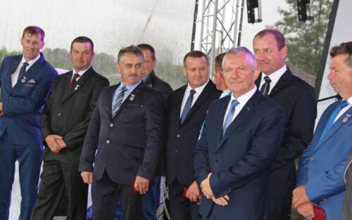 Zdjęcie przedstawia grupę osób  stojących na scenie