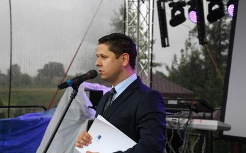 Zdjęcie przedstawia człowieka mówiącego przez mikrofon stojąc na scenie