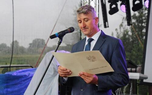 Zdjęcie przedstawia mężczyznę mówiącego przez mikrofon