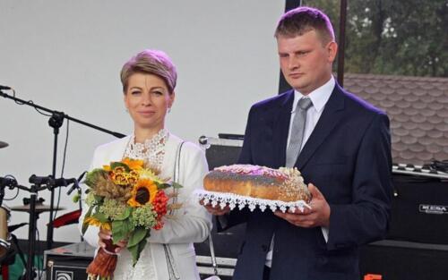 Zdjęcie przedstawia dwóch osób stojących przed mikrofonem na scenie