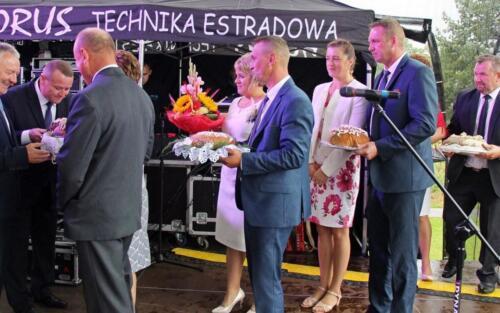 Zdjęcie przedstawia stojących z jedzeniem ludzi