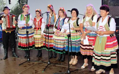 Zdjęcie przedstawia śpiewającą grupę kobiet ubranych w stroje świąteczne