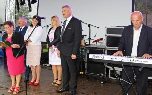 Zdjęcie przedstawia stojących na wydarzeniu świątecznym ludzi przed mikrofonami
