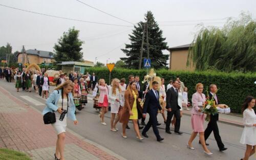 Zdjęcie prezentuje idącą grupę ludzi ubranych w stroje świąteczne