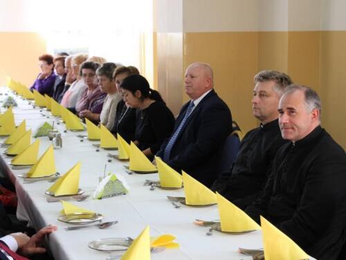 Zdjęcie przedstawia starych ludzi siedzących przy stole.