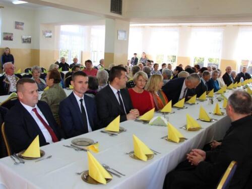 Zdjęcie przedstawia ludzi siedzących przy stole.