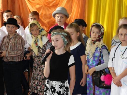Zdjęcie przedstawia małe dzieci które śpiewają i tańczą podczas przedstawienia.