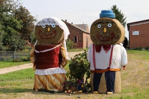 Zdjęcie przedstawia dwie stojące na ulicę lalki zrobione z siana