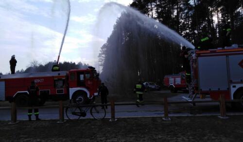 Obrazek przedstawia strażaków którzy ćwiczą gaszenie pożaru.