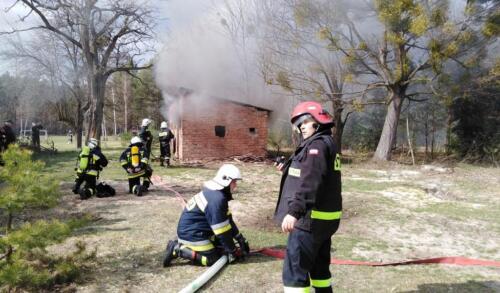 Obrazek przedstawia strażaków ćwiczących gaszenie pożaru.