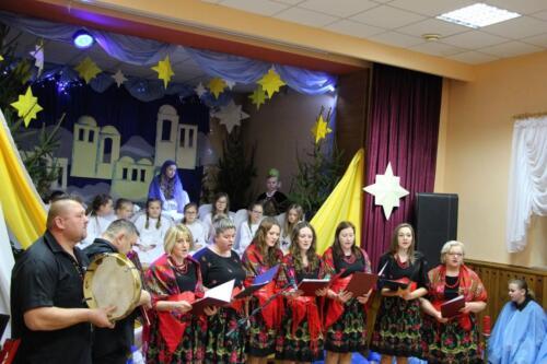 Zdjęcie przedstawia zespół ludowy wykonujący utwór.