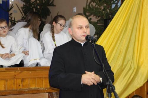 Zdjęcie przedstawia mówiącego księdza a w tle widać postacie z jasełek.