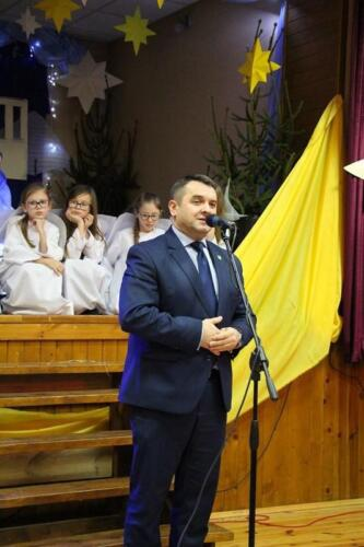 Zdjęcie przedstawia mówiącego człowieka a w tle widać postacie z jasełek.