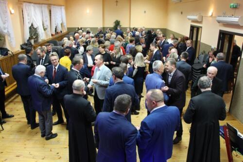 Obraz przedstawia grupę osób na gminnym spotkaniu opłatkowym