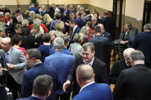Zdjęcie przedstawia ludzi na spotkaniu opłatkowym.